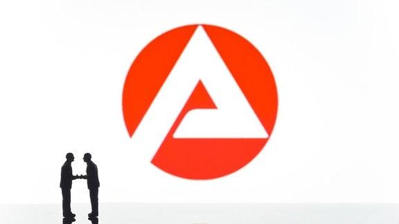 Zwei Figuren vor dem Logo der Arbeitsagentur