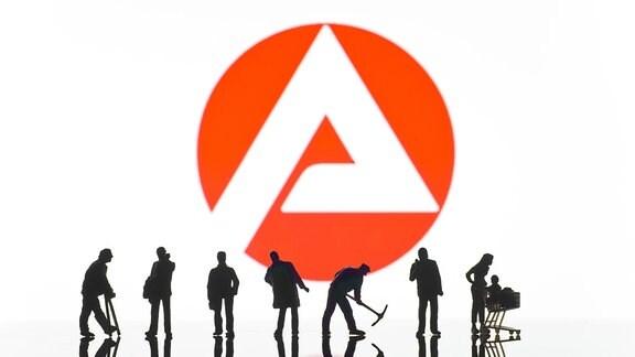 Figuren vor dem Logo der Arbeitsagentur