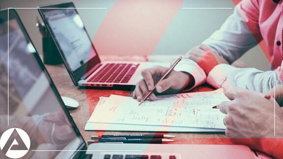 Zwei Männer sitzen mit Laptops und einem Schreibblock in einem Büro.