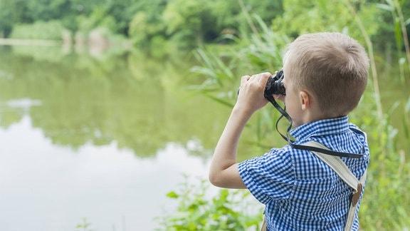 Ein Junge an einem See schaut durch ein Fernglas.