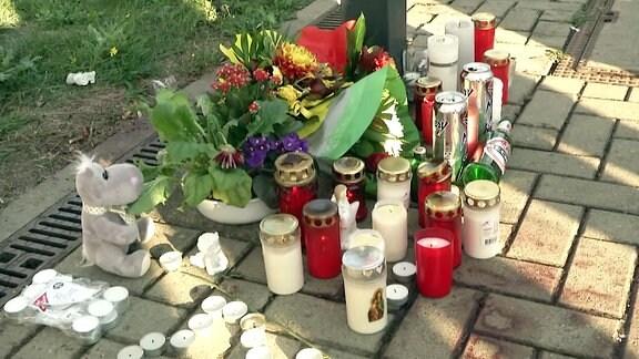 Mehrere Kerzen stehen auf einem Bahnsteig