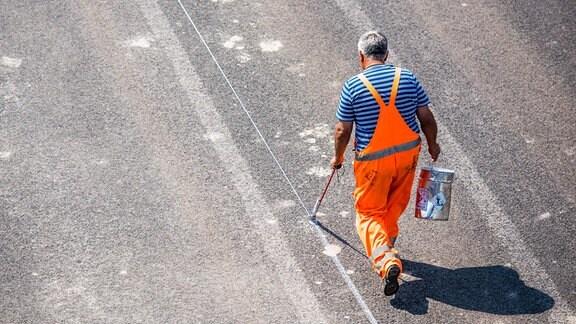 Ein Mann bemalt eine Straße.