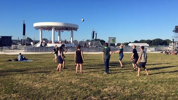Jugendliche spielen auf einer Wiese mit dem Volleyball