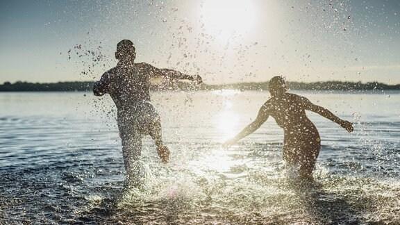ein Mann und eine Frau laufen bei Sonnenuntergang ins spritzende Wasser