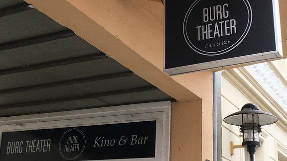 """Der Eingangsbereich des Kinos """"Burg-Theater"""" mit Eingangsschildern"""