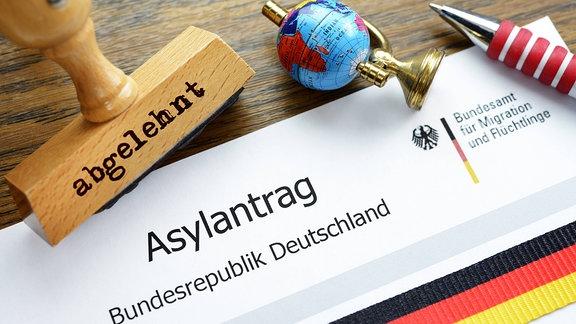 Asylantrag und ein Stempel mit der Aufschrift - abgelehnt -