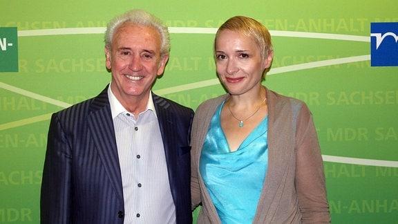 Ein Mann und eine Frau stehen vor einer grünen Wand