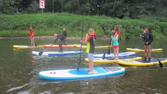 Kinder paddeln auf Brettern auf einem Fluss