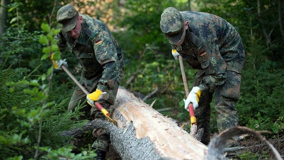 Soldaten der Bundeswehr entrinden einen Baumstamm.