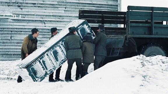 Soldaten heben Kiste auf LKW-Ladefläche