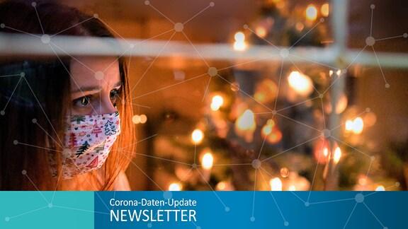 Eine Frau mit Mund-Nasenschutz-Maske schaut sehnsüchtig aus dem Wohnzimmerfenster, innen brennen die Kerzen des Weihnachstbaumes.