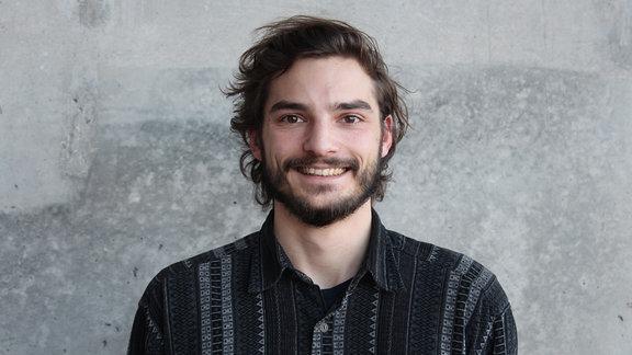 Daniel Tautz vor einer grauen Wand