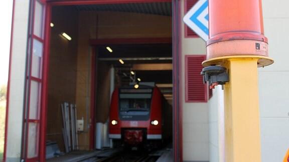 ein roter Zug fährt aus einer Halle heraus