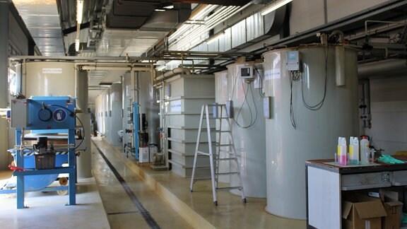 mehrere graue Zylinder stehen in einer Halle