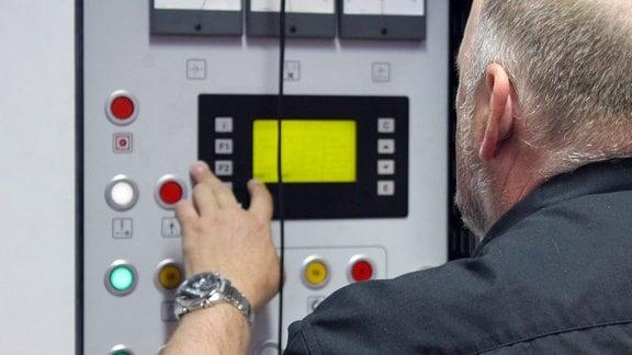 Ein Mann drückt Knöpfe am Diagnosesystem eines Zuges