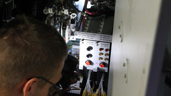 Ein Mann leuchtet mit einer Taschenlampe auf elektrische Bauteile
