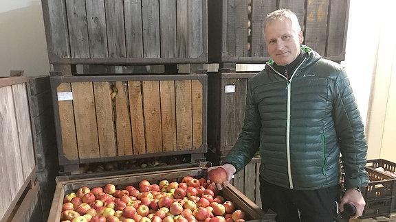 Mann steht neben einer großen Kiste mit Äpfeln und hält einen Apfel in der Hand.