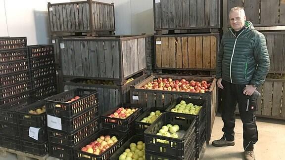 Ein Mann steht neben einer Kisten mit Äpfeln.