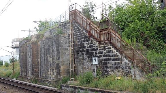 Entlang einer elektrifizierten Bahnstrecke führt eine Treppe mit rostigem Geländer eine Mauer hinauf.