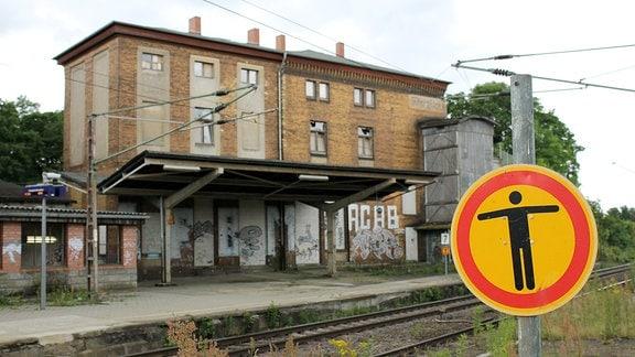 Ein Schild weist darauf hin, dass der Durchgang verboten ist, im Hintergrund ein dreigeschossiges Bahnhofsgebäude.
