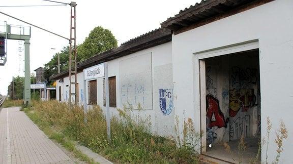 Ein Bahnsteig mit gemauertem Wartehäuschen, dessen Fenster mit Brettern vernagelt sind.