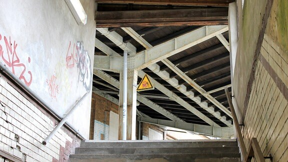 Blick aus einem Tunnel hinaus auf ein Bahnsteigdach mit rostigen Trägern.