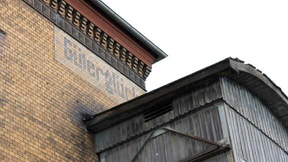 """Blasser Schriftzug """"Güterglück"""" unter der Dachkante eines Bahnhofsgebäudes."""