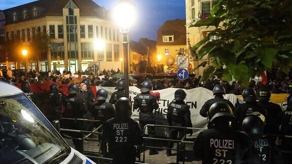 Linke Demonstranten stehen hinter einer Polizeiabsperrung am Marktplatz in Köthen und erwarten die Teilnehmer der AfD Demo auf dem Marktplatz in Köthen.