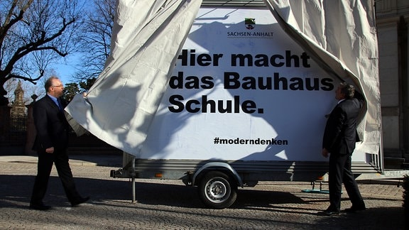 Ministerpräsident Reiner Haseloff (l.) enthüllt das neue Bauhaus-Plakat