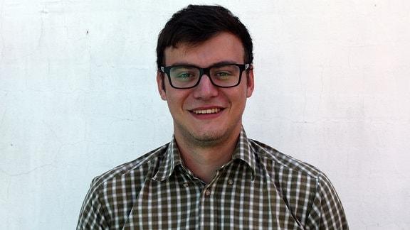 Porträtaufnahme eines jungen Mannes, dunkle Haare, schwarze Brille und kariertes Hemd, der vor einer weißen Wand steht und lächelt