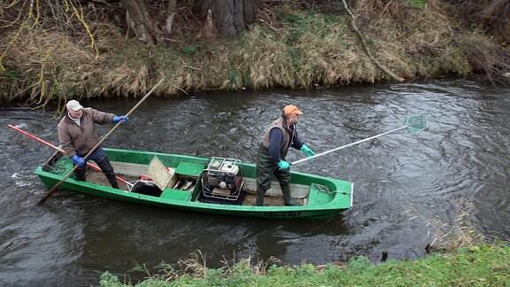 Robert Frenzel und Ingo Borkmann (v.l.) vom Institut für Binnenfischerei Potsdam in einem grünen Kahn auf einem Fluss