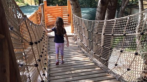 Ein Mädchen läuft eine Hängebrücke nach unten.