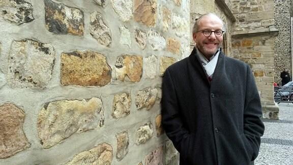 Ein Mann mit Schal und anthrazitfarbenem Mantel lehnt an einer Außenwand einer Kirche
