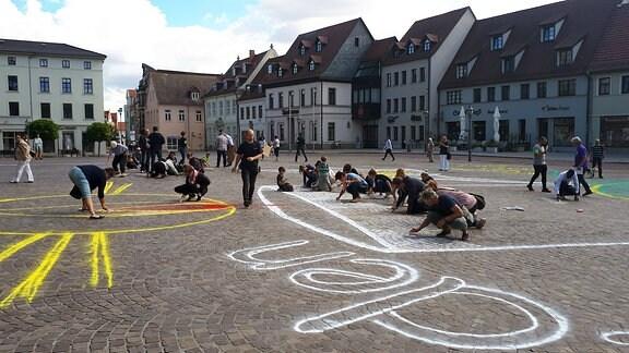 Mehrere Menschen knien auf dem Marktplatz in Köthen und malen mit Kreide