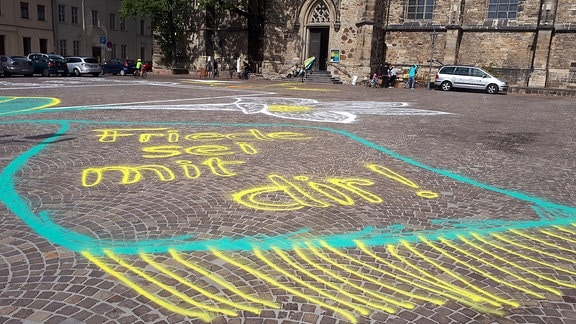 Vor einer Kirche in Köthen steht mit Kreide auf Pflastersteine geschrieben: Friede sei mit dir