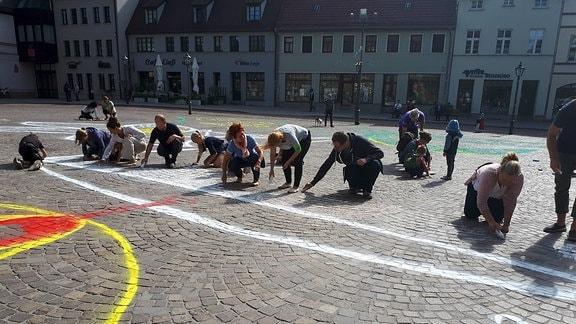 Menschen malen mit Kreide auf dem Marktplatz in Köthen