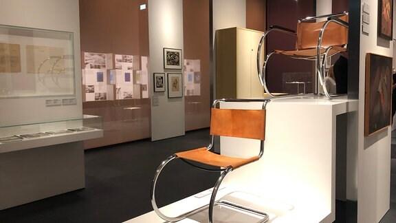 Zwei Stühle stehen im Bauhaus Museum in Dessau in einem Ausstellungsraum, im Hintergrund Bilder und Informationstafeln