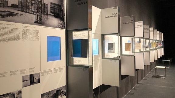 Blick in einen Ausstellungsraum im Bauhaus Museum, in dem mehrere Glaskästen mit Informationstafeln aus der Wand hervorragen
