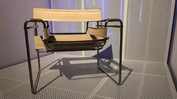 Ein Stuhl mit durchhängender Sitzfläche steht in einer Ausstellung im Bauhaus Museum in Dessau