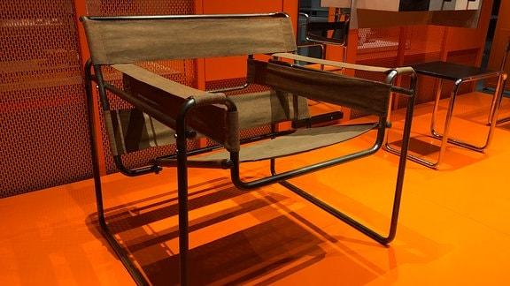 Ein Stuhl mit durchhängender Sitzfläche steht im Bauhaus Museum in Dessau auf orangenem Boden