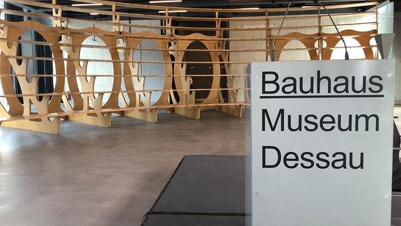 Auf einem Schild steht -Bauhaus Museum Dessau-, im Hintergrund eine hölzerne Sitzkonstruktion