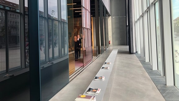 Blick auf einen Gang im Bauhaus Museum in Dessau, rechts eine Glasfassade, im Hintergrund zwei Menschen