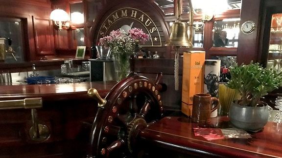 Bar mit Schiffsruder, Glocke, Blumen und weiterer Deko