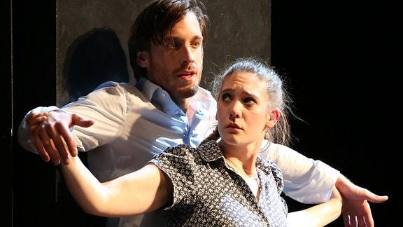 Eine Schauspielerin und ein Schauspieler stehen mit ausgestreckten Armen gemeinsam auf der Bühne.