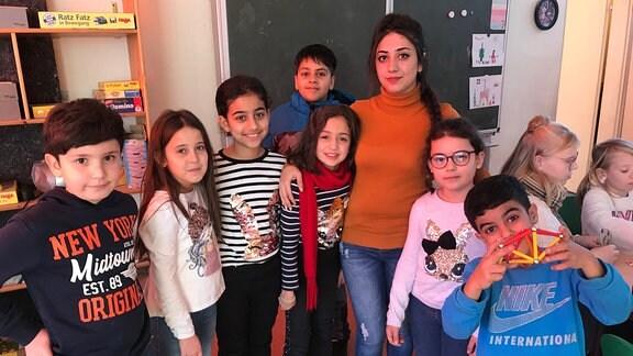 Mehrere Hort-Kinder aus Dessau mit der Sprach- und Kulturmittlerin Simav Naser