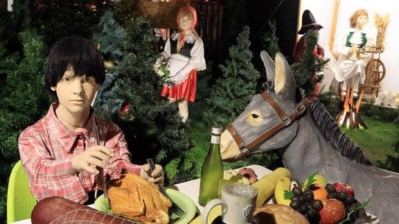 Märchenfigur sitzt an einem gedeckten Tisch