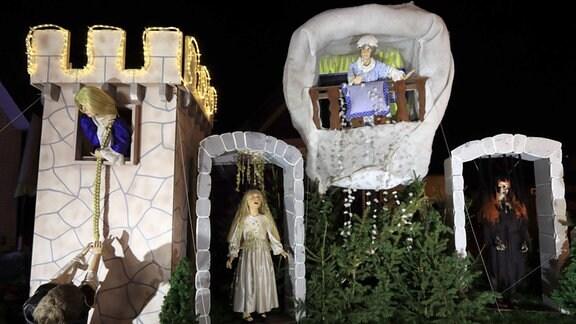 Märchenfiguren in einem Vorgarten - Szene aus Frau Holle und Dornröschen