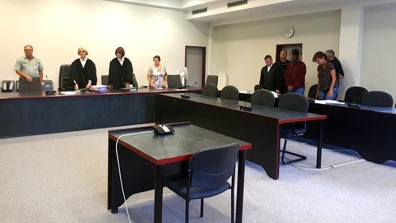 Mehrere Personen stehen im Gerichtssaal des Landgerichts Dessau
