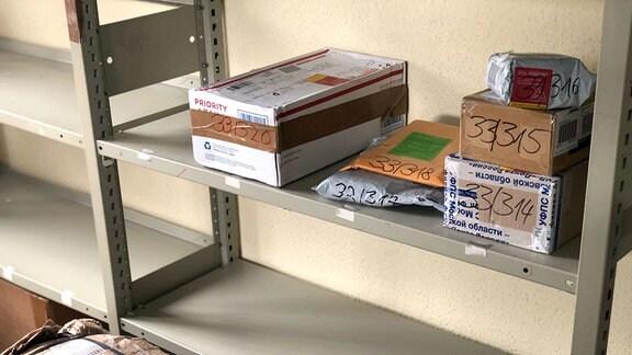 Pakete liegen in einem Regal.