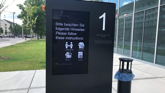 Corona-Hinweisschild vor Bauhaus-Museum